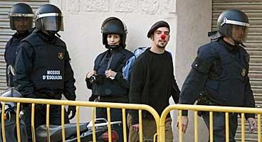 Un dels ocupants de Can Ricart surt de la nau custodiat per diversos mossos, ahir. FOTO: LAURA GUERRERO